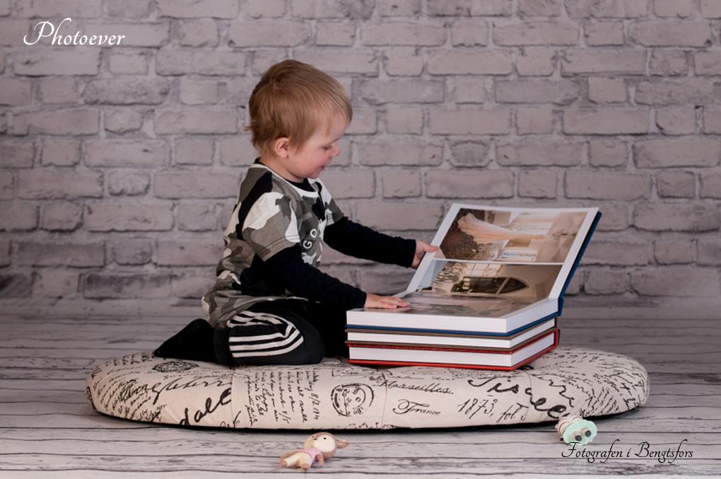 en pojke tittar i fotoböcker från Photoever